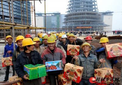 """▲春节临近,""""一院两馆""""仍有500多名建设者坚守工地加紧施工。收到志愿者送来的""""春节大礼包"""",他们非常开心。  记者何平江 摄"""