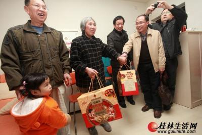 """▲志愿者把爱心企业赠送的""""春节大礼包""""送到象山区民族社区一困难老党员家中。记者刘教清 摄"""