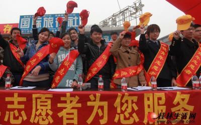 参与活动的志愿者在火车站挥帽欢送返乡农民工。记者刘教清 摄
