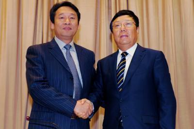 刘君同志(左)与赵乐秦同志(右)亲切握手。 记者唐艳兰 摄