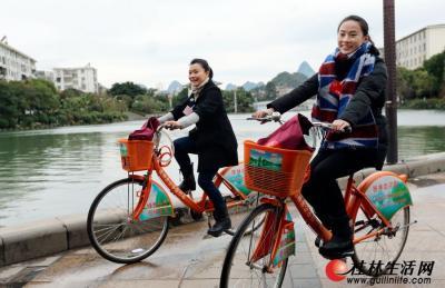 回家乡参加政协桂林市第四届委员会第三次会议的市政协委员莫慧兰(左)和李婷(右)骑单车往返会场和宾馆,以实际行动践行低碳环保,建设美丽桂林。记者唐侃 摄