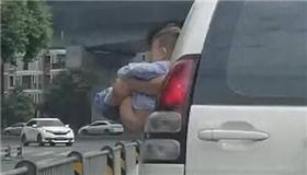 危险!汽车行进中男孩被抱出车窗外撒尿